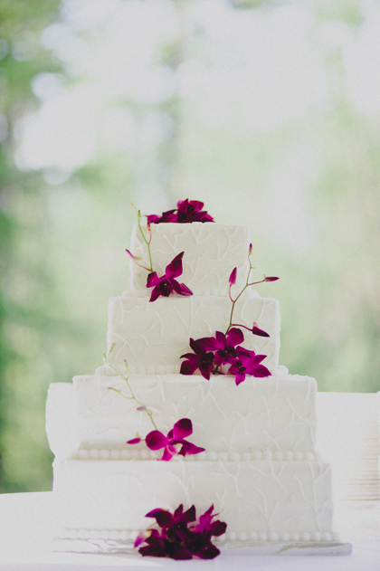 White wedding cake with purple orchids